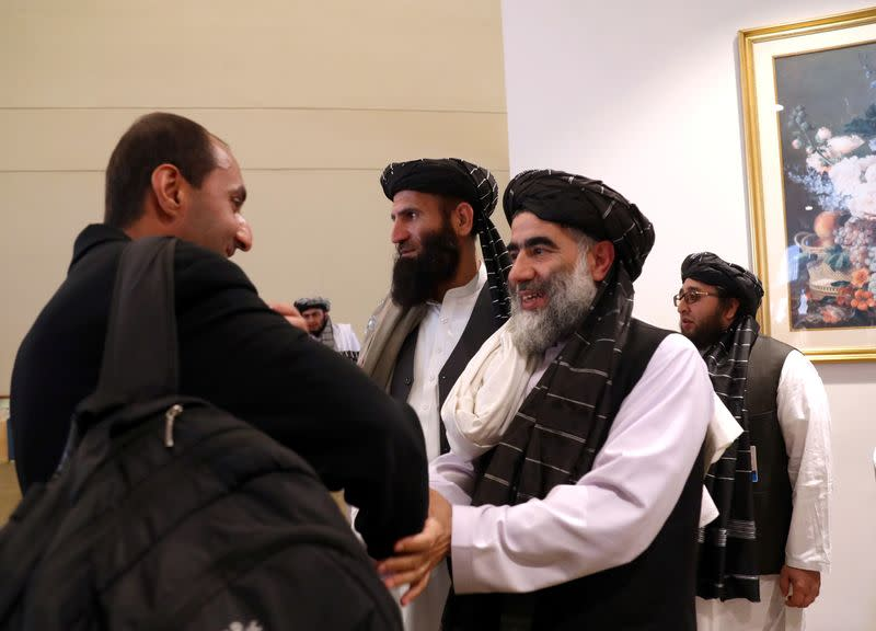 FILE PHOTO: Members of Afghanistan's Taliban delegation (R) gather ahead of an agreement signing between them and U.S. officials in Doha