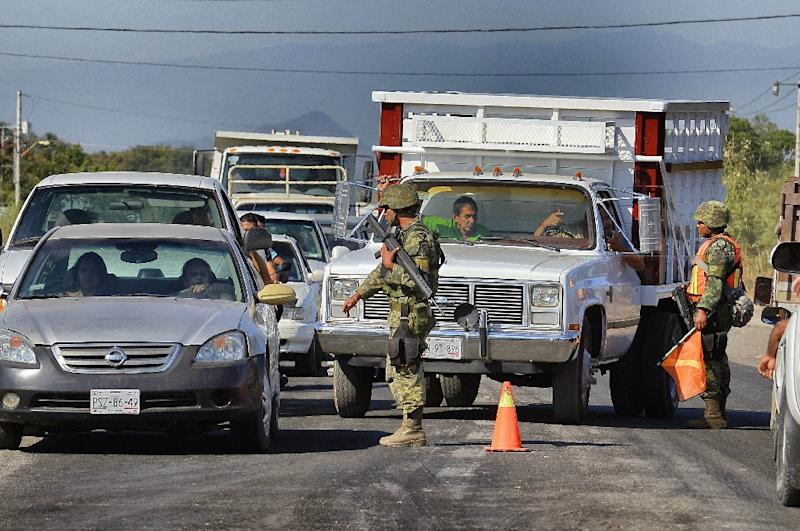 Mexican soldiers inspect vehicles in a checkpoint at the entrance of the Apatzingan community, state of Michoacan, Mexico on January 12, 2015 (AFP Photo/Alfredo Estrella)