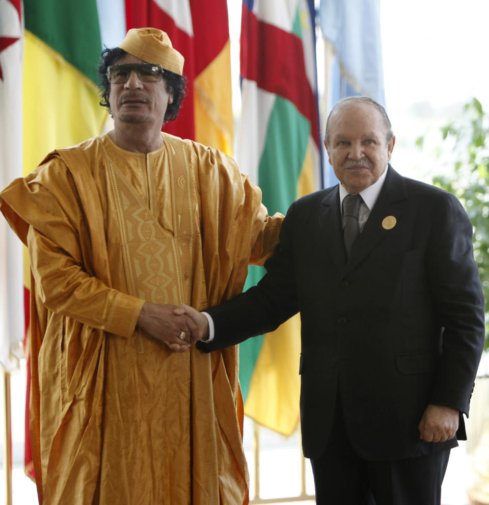 FILE - In this July 1, 2009 file photo, Libyan leader Moammar Gadhafi, left receives Algerian President Abdelaziz Bouteflika ahead of the opening session of the 13th African Union summit of heads of state and government in Sirte, Libya. Former Algerian President Bouteflika, who fought for independence from France in the 1950s and 1960s and was ousted amid pro-democracy protests in 2019 after 20 years in power, has died at age 84, state television announced Friday, Sept. 17, 2021. (AP Photo/Nasser Nasser, File)