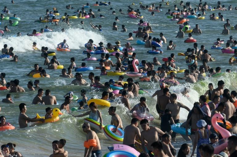 Crowds of holidaymakers in Qingdao wade into the water and bob alongside each other with their trusty floats, beating the hot August sun (AFP Photo/FRED DUFOUR)