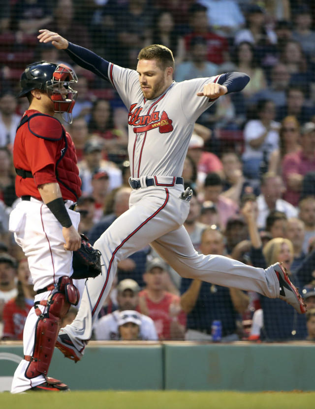 Atlanta Braves' Freddie Freeman, right, scores in front of Boston Red Sox catcher Christian Vazquez, left, on a two-run double by Nick Markakis in the third inning of an interleague baseball game at Fenway Park, Friday, May 25, 2018, in Boston. (AP Photo/Elise Amendola)