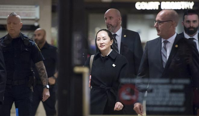 Meng Wanzhou, chief financial officer of Huawei, leaves the British Columbia Supreme Court in Vancouver on Thursday, surrounded by guards. Photo: AP