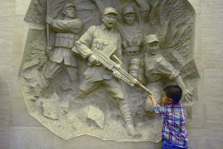 A boy inspects a mural during a 2014 visit to China's Anti-Japanese War museum in west Beijing