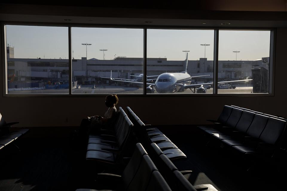 A passenger sits in Terminal 4 at Los Angeles International Airport
