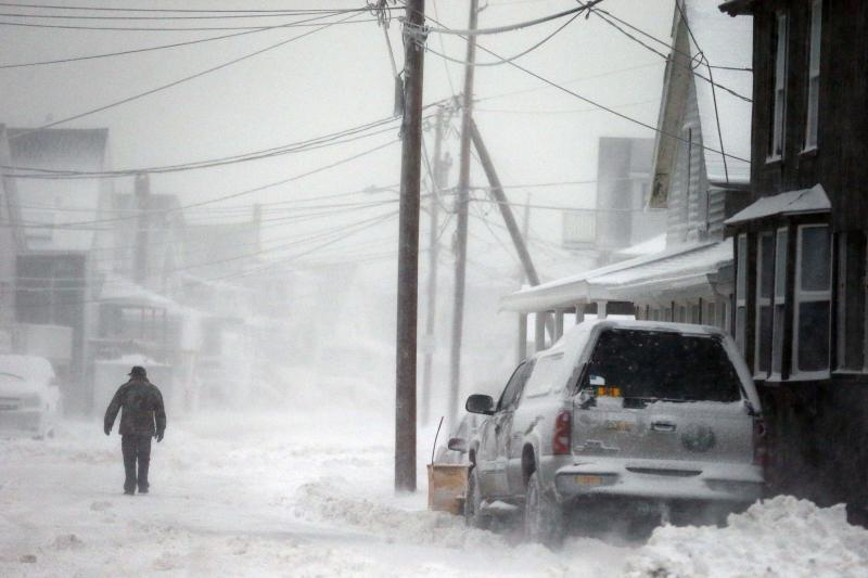 A man walks in the snow down a road along the shore in Scituate, Mass., Friday, Jan. 3, 2014. A winter storm slammed into the U.S. Northeast with howling winds and frigid cold, dumping nearly 2 feet (60 centimeters) of snow in some parts and whipping up blizzard-like conditions Friday. (AP Photo/Michael Dwyer)