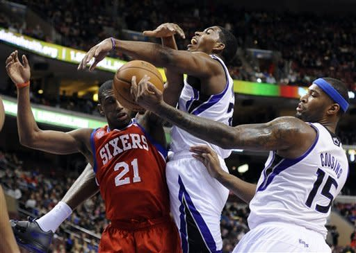 Sacramento Kings' DeMarcus Cousins (15) grabs the loose ball in front of Philadelphia 76ers' Thaddeus Young (21) and Kings' Jason Thompson (34), of the Dominican Republic, during the first half of an NBA basketball game, Friday, Feb. 1, 2013, in Philadelphia. (AP Photo/Michael Perez)