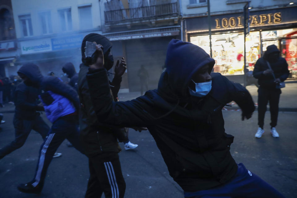 A protestor throws stones toward a police office in the Belgium capital, Brussels, Wednesday, Jan. 13, 2021, at the end of a protest asking for authorities to shed light on the circumstances surrounding the death of a 23-year-old Black man who was detained by police last week in Brussels. The demonstration in downtown Brussels was largely peaceful but was marred by incidents sparked by rioters who threw projectiles at police forces and set fires before it was dispersed. (AP Photo/Francisco Seco)
