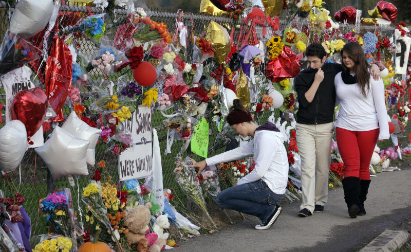 FILE--In this Oct. 29, 2014, file photo, Dana Pattie, left, kneels at a block-long fence at Marysville-Pilchuck High School memorializing a shooting there last week as a couple walks past in Marysville, Wash. Recent mass shootings spurred Congress to try to improve the background check system used during gun purchases, but experts say the system is so fractured that federal legislation being considered in Washington D.C. will do little to help keep weapons out of the hands of dangerous people. (AP Photo/Elaine Thompson, file)