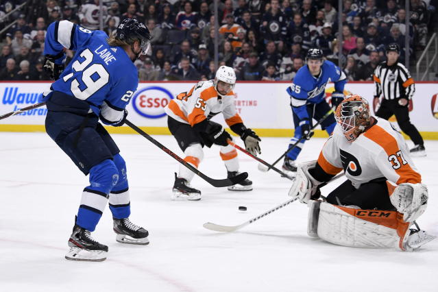 Winnipeg Jets' Patrik Laine (29) tries to pass the puck over to Mark Scheifele (55) past Philadelphia Flyers goaltender Brian Elliott (37) during second-period NHL hockey game action in Winnipeg, Manitoba, Sunday, Dec. 15, 2019. The puck deflected off Flyers' Shayne Gostisbehere (53) for a goal. (Fred Greenslade/The Canadian Press via AP)