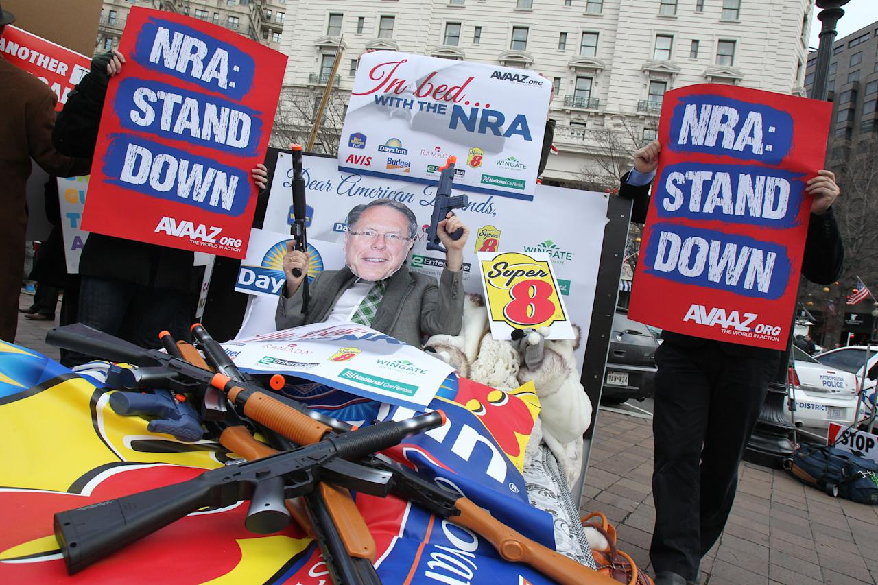 "IMAGE DISTRIBUTED FOR AVAAZ - Members of the activist group Avaaz protest today's NRA press conference with a likeness of NRA CEO Wayne LaPierre Jr., calling on NRA affiliates like Days Inn and Super 8 to get ""out of bed"" with the gun lobby, outside the Willard Hotel in Washington, Friday, Dec. 21, 2012. (Paul Morigi / AP Images for Avaaz)"
