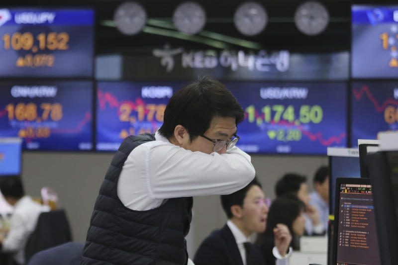 A currency trader covers his mouth at the foreign exchange dealing room of the KEB Hana Bank headquarters in Seoul, South Korea, Wednesday, Jan. 29, 2020. Shares are mostly higher in Asia after a rebound on Wall Street that reversed most losses from a sell-off the day before. (AP Photo/Ahn Young-joon)