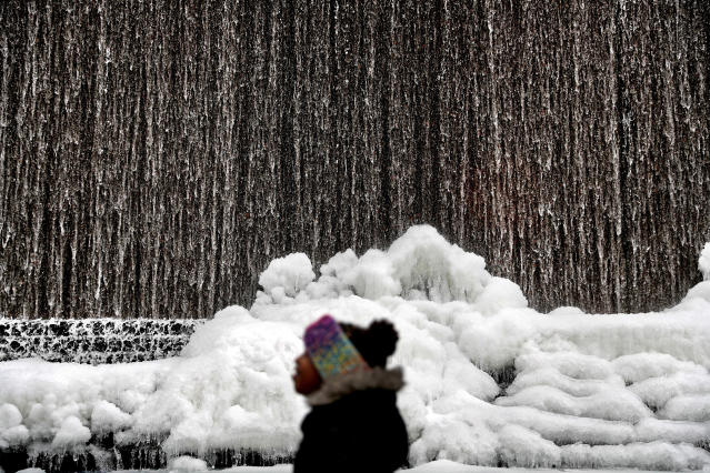 <p>Alora Freeman, 8, watches as ice builds along a downtown water fountain in Atlanta, Wednesday, Jan. 3, 2018. A brutal winter storm scattered a wintry mix of snow, sleet and freezing rain from normally balmy north Florida up the Southeast seaboard Wednesday, adding to the misery of a bitter cold snap. (Photo: David Goldman/AP) </p>