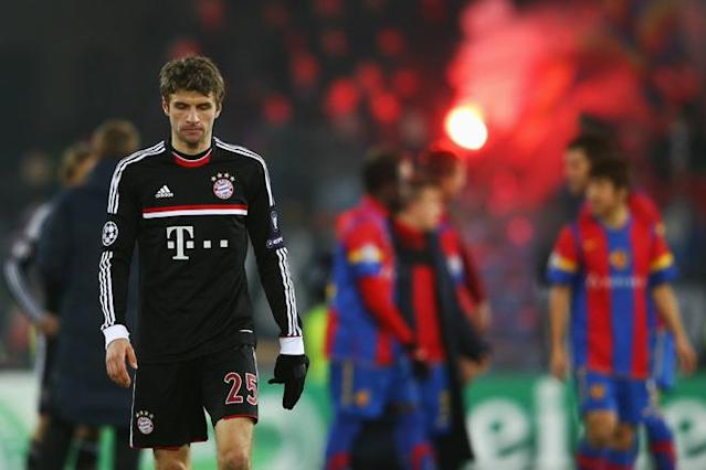 BASEL, SWITZERLAND - FEBRUARY 22: Thomas Mueller of Muenchen reacts as players of Basel celebrate after the UEFA Champions League Round of 16 first leg match between FC Basel 1893 and FC Bayern Muenchen at St. Jakob-Park on February 22, 2012 in Basel, Switzerland. (Photo by Alex Grimm/Bongarts/Getty Images)