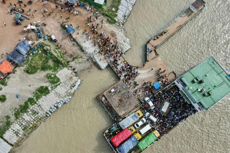 People disembark from a ferry to return to work as the Bangladesh government relaxed the lockdown for all export oriented factories