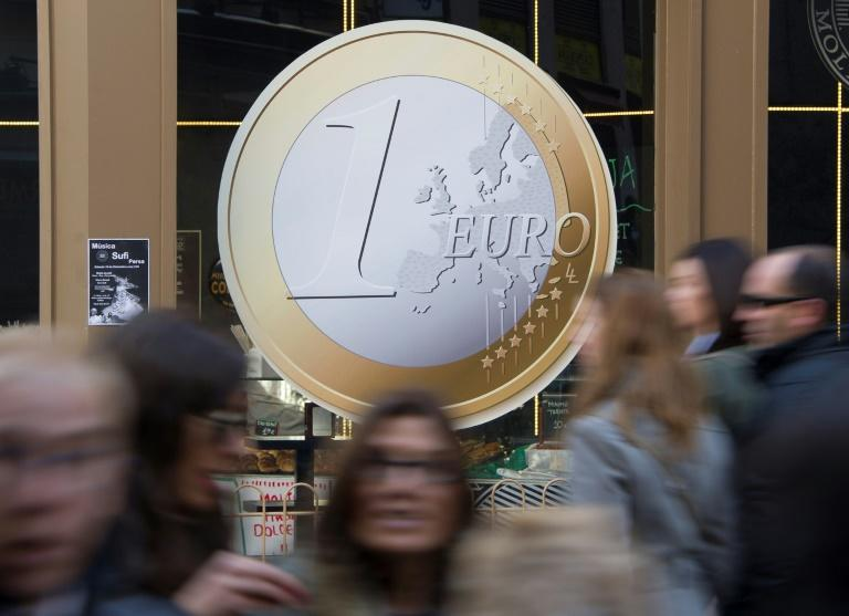 People walk in front of a restaurant displaying a giant sticker of a Euro coin on its window and offering pizzas for one euro in the center of Madrid on December 08, 2011. France and Germany drummed up support for their plan to fix the eurozone as European leaders geared up for a last chance summit to save the debt-laden currency union from collapse.AFP PHOTO/DOMINIQUE FAGETPeople walk in front of a restaurant displaying a giant sticker of a Euro coin on its window and offering pizzas for one euro in the center of Madrid on December 08, 2011. France and Germany drummed up support for their plan to fix the eurozone as European leaders geared up for a last chance summit to save the debt-laden currency union from collapse.AFP PHOTO/DOMINIQUE FAGET