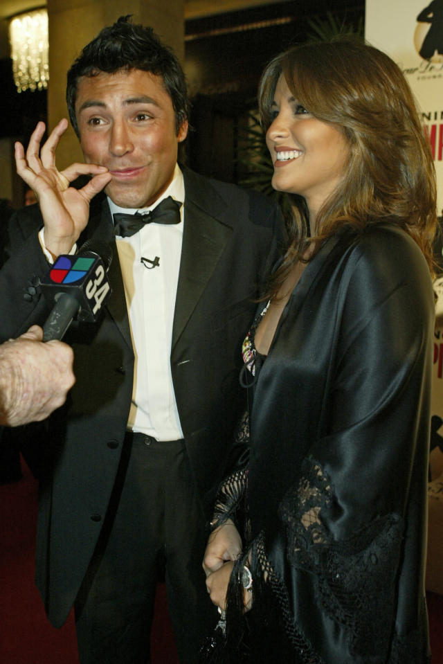 FILE - In this Nov. 16, 2004 file photo, boxer Oscar De La Hoya and his wife, Millie Corretjer, arrive to the 8th Annual Evening of Champions presented by the Oscar de la Hoya Foundation, in Beverly Hills, Calif. De La Hoya got drunk the night he won the only boxing gold for the U.S. in the 1992 Olympics, and was still drinking when he lost his last fight to Manny Pacquiao. Now sober after a second stint in rehab he's in a fight of another kind for control of his boxing company. (AP Photo/Damian Dovarganes, File)