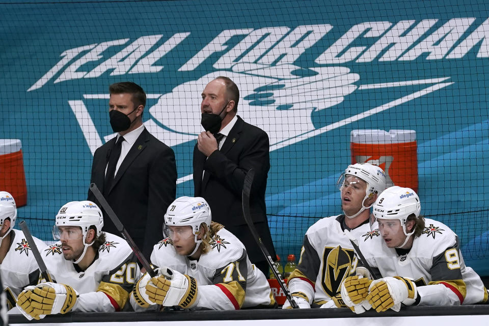 Vegas Golden Knights coach Peter DeBoer, top right, watches from the bench during the second period of the team's NHL hockey game against the San Jose Sharks in San Jose, Calif., Saturday, March 6, 2021. (AP Photo/Jeff Chiu)