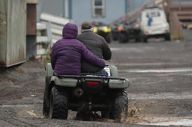 A couple drives through the streets on their ATV in Kivalina, Alaska, a Native coastal village where there are few vehicles.