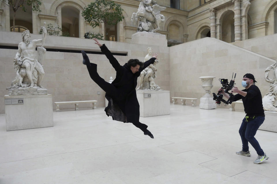 Dancer Germain Louvet performs during the filming of a commercial, in the Louvre museum, in Paris, Thursday, Feb. 11, 2021. Though empty corridors and vacant galleries are a grim sight for frustrated art-lovers, they are a golden opportunity to do works of renovation, refurbishment and re-ordering that were simply not possible with the around 10 million visitors per year. (AP Photo/Thibault Camus)