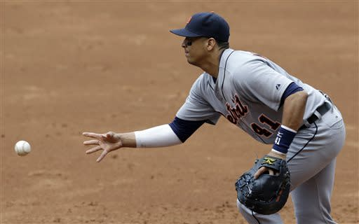 Detroit Tigers' Victor Martinez tosses the ball to pitcher Doug Fister at first base to get Cleveland Indians' Carlos Santana out in the third inning of a baseball game on Sunday, July 7, 2013, in Cleveland. (AP Photo/Tony Dejak)