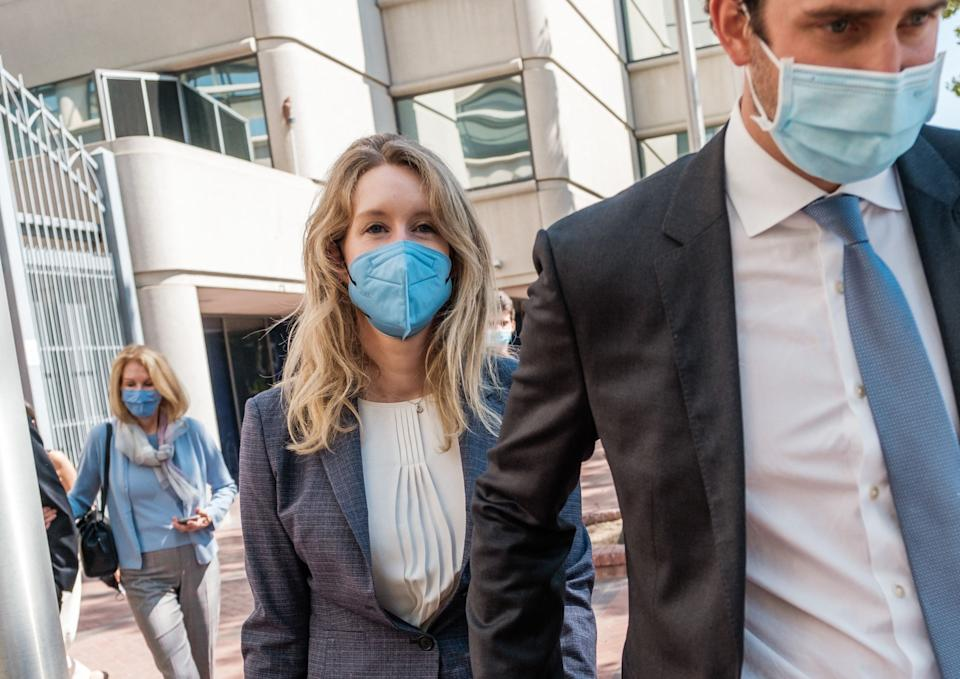 Elizabeth Holmes (L), founder and former CEO of blood testing and life sciences company Theranos, leaves the courthouse with her husband Billy Evans after the first day of her fraud trial in San Jose, California on September 8, 2021. - California jurors tasked with deciding whether fallen biotech star Elizabeth Holmes is guilty of a stunning fraud or is herself a victim were set to hear opening arguments in her trial on September 8, 2021. Federal prosecutors in the heart of Silicon Valley have in their filings portrayed Holmes as a villain who swindled investors in the diagnostics company Theranos -- which she founded at age 19 -- with tests that did not work. (Photo by Nick Otto / AFP) (Photo by NICK OTTO/AFP via Getty Images)