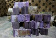 FILE PHOTO: Syrian pounds are pictured inside an exchange currency shop in Azaz