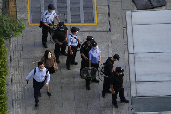 Residents past by police and security personnel preparing for duty outside the Evergrande headquarters in Shenzhen, China, Friday, Sept. 24, 2021. Things appeared quiet at the headquarters of the heavily indebted Chinese real estate developer Evergrande, one day after the day it had promised to pay interest due to bondholders in China. (AP Photo/Ng Han Guan)