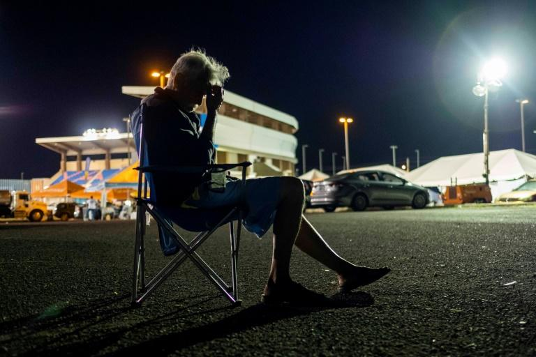 A man sits on a camping chair at a tent city shelter in a baseball stadium parking lot in Yauco, Puerto Rico on January 14, 2020, after a powerful earthquake hit the island