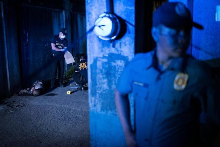 Police gather evidence during a shooting by unidentified gunmen in Manila.