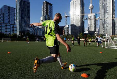 People play soccer in front of the skyline in one of the host cities for the 2026 FIFA World Cup, in Toronto