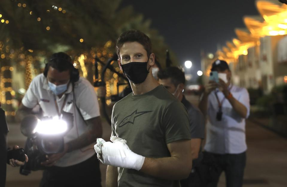 FILE - Haas driver Romain Grosjean of France arrives to the paddock to thank the marshals in Bahrain International Circuit in Sakhir, Bahrain, in this Thursday, Dec. 3, 2020, file photo. Grosjean escaped with only minor burns when his Haas car exploded into a fireball after crashing on the first lap at the Bahrain GP. Mercedes announced Wednesday, May 5, 2021, that Grosjean will drive Lewis Hamilton's 2019 championship-winning car at the French Grand Prix on June 27 before a full test day at Circuit Paul Ricard two days later. (AP Photo/Kamran Jebreili, File)