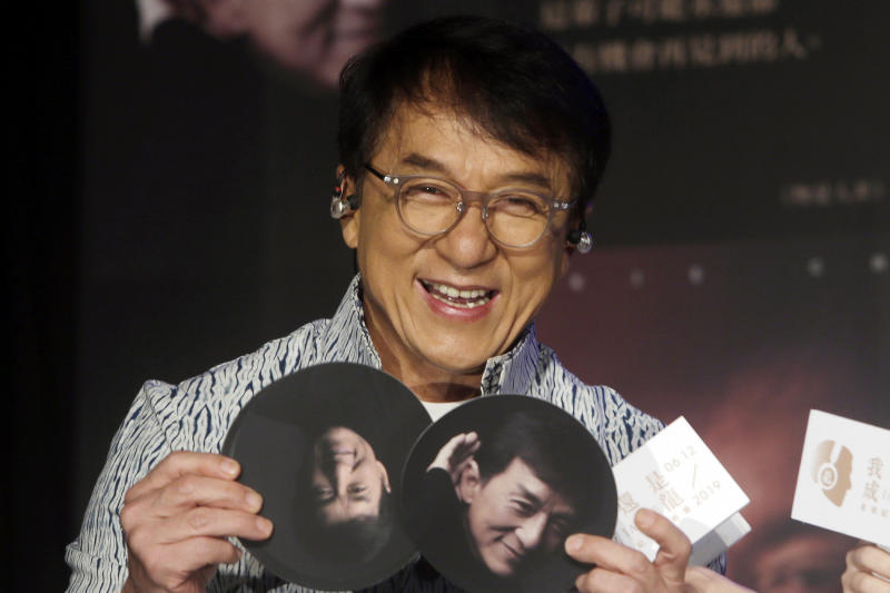 "FILE - In this June 12, 2019, file photo, Hong Kong actor and singer Jackie Chan shows photos during a promotional event announcing his new album ""I AM ME"" in Taipei, Taiwan. A visit by Chan to Vietnam has been cancelled following complaints over his alleged pro-China stance on South China Sea sovereignty issues. (AP Photo/Chiang Ying-ying, File)"