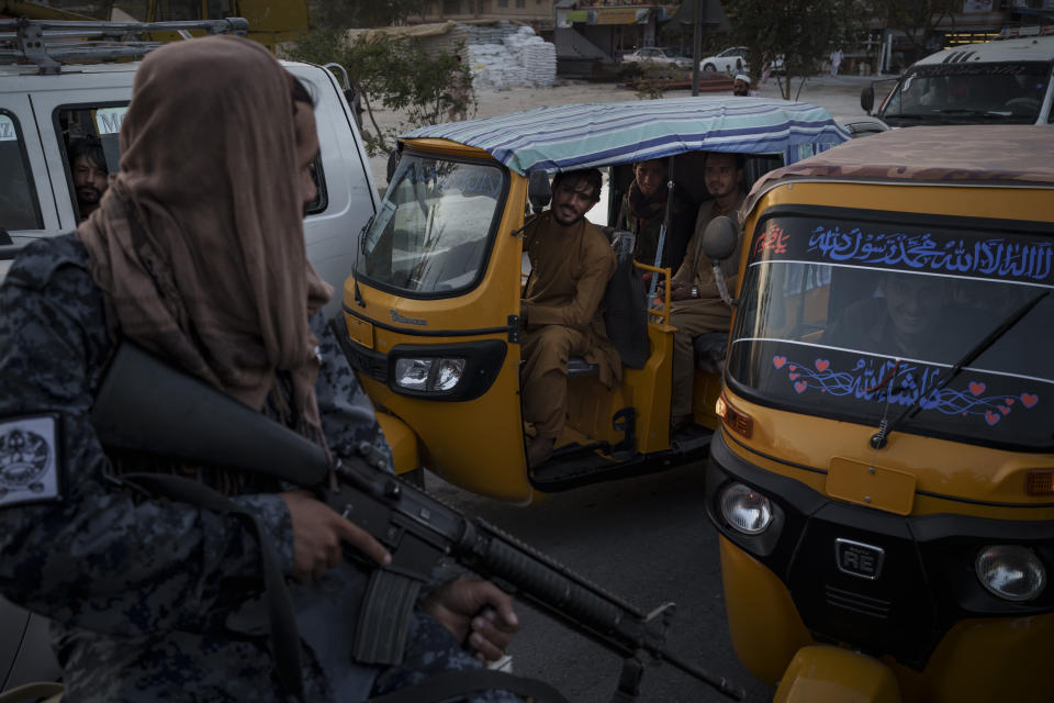 Afghan drivers and passengers stuck in a traffic jam look at Taliban fighters riding in the back of a pickup truck in Kabul, Afghanistan, Monday, Sept. 20, 2021. (AP Photo/Felipe Dana)