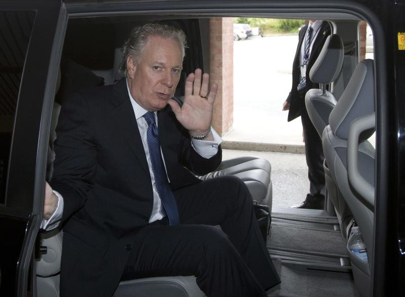 Quebec Liberal Party Leader Jean Charest waves as he leaves a hotel in Sherbrooke, Quebec, Canada on Wednesday, Sept. 5, 2012. A masked gunman wearing a blue bathrobe opened fire during a midnight victory rally for Quebec's new premier, killing one person and wounding another. The new premier, Pauline Marois of the separatist Parti Quebecois, was whisked off the stage by guards while giving her speech and uninjured. It was not clear if the gunman was trying to shoot Marois, whose party favors separation for the French-speaking province from Canada. Police identified the gunman only as a 62-year-old man, and were still questioning him Wednesday morning. (AP Photo/The Canadian Press, Jacques Boissinot)