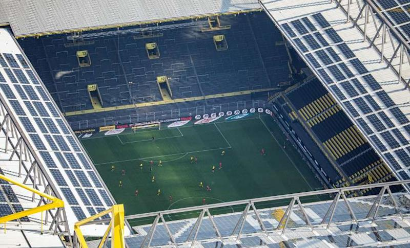 In this aerial image soccer players of both teams play the game in front of empty spectator stands during the German Bundesliga soccer match between Borussia Dortmund and FC Bayern Munich in Dortmund, Germany, Tuesday, May 26, 2020. The German Bundesliga is the world's first major soccer league to resume after a two-month suspension because of the coronavirus pandemic. (Marcel Kusch/DPA via AP, Pool)