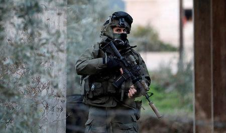 Member of Israeli armed forces is seen during a raid in the West Bank city of Jenin