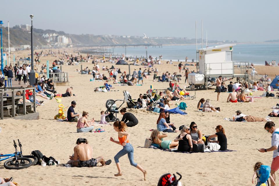 Members of the public enjoy the beach in Bournemouth, southwest England as a spell of warm weather covers the country on March 30, 2021. (Photo by Adrian DENNIS / AFP) (Photo by ADRIAN DENNIS/AFP via Getty Images)
