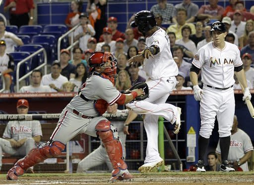 Miami Marlins Jose Reyes evades Philadelphia Phillies catcher Carlos Ruiz as he cross home plate in the third inning of a baseball game in Miami, on Saturday, June 30, 2012 (AP Photo/Terry Renna)