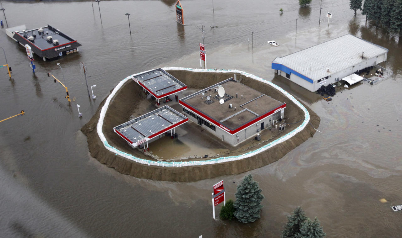 In this aerial photo, a Conoco gas station is surrounded by sand bags, the flood waters of the Souris River, and an oil slick Friday, June 24, 2011 in Minot, N.D. North Dakota Gov. Jack Dalrymple says the Souris River is flowing over most levees in Minot as it surges past a 130-year-old record level. (AP Photo/Charles Rex Arbogast)