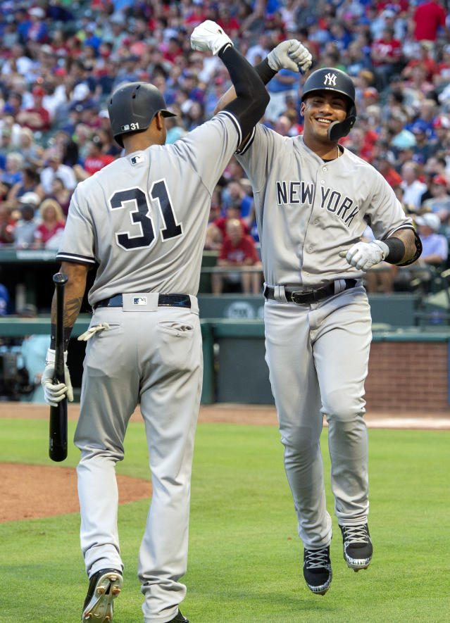 New York Yankees' Gleyber Torres, right, is congratulated by Aaron Hicks (31) after hitting a solo home run off Texas Rangers starting pitcher Cole Hamels during the third inning of a baseball game Tuesday, May 22, 2018, in Arlington, Texas. (AP Photo/Jeffrey McWhorter)