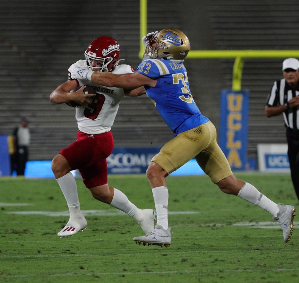 Fresno State quarterback Jake Haener extends his arm to UCLA linebacker Bo Calvert as he scampers for extra yardage.
