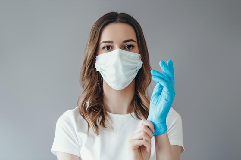 woman patient in a medical mask puts on protective surgical sterile gloves on her arm