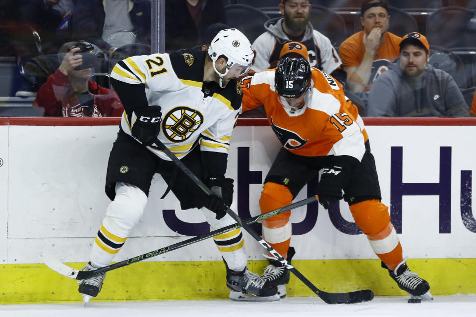 Boston Bruins' Nick Ritchie, left, and Philadelphia Flyers' Matt Niskanen battle for the puck during the second period of an NHL hockey game, Tuesday, March 10, 2020, in Philadelphia. (AP Photo/Matt Slocum)