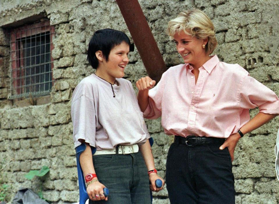 """FILE - In this file photo dated Sunday Aug. 10, 1997, Britain's Diana, Princess of Wales, right, speaks with 15-year old landmine victim Bosnian muslim girl Mirzeta Gabelic, in front of Mirzeta's home in Sarajevo, while Diana was on a visit to the region as part of her campaign against landmines. For someone who began her life in the spotlight as """"Shy Di,"""" Princess Diana became an unlikely, revolutionary during her years in the House of Windsor. She helped modernize the monarchy by making it more personal, changing the way the royal family related to people. By interacting more intimately with the public -- kneeling to the level of children, sitting on edge of a patient's hospital bed, writing personal notes to her fans -- she set an example that has been followed by other royals as the monarchy worked to become more human and remain relevant in the 21st century. (AP Photo /Hidajet Delic, File)"""