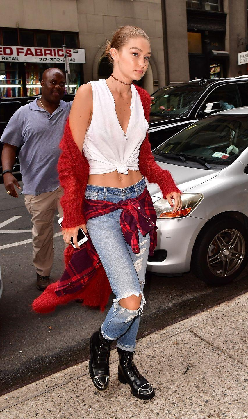 <p>The sweltering temps in NYC this weekend didn't stop Gigi from embracing fall style. The model stepped out in a fuzzy red cardigan and distressed denim with a plaid flannel tied around her waist and black leather combat boots. </p>