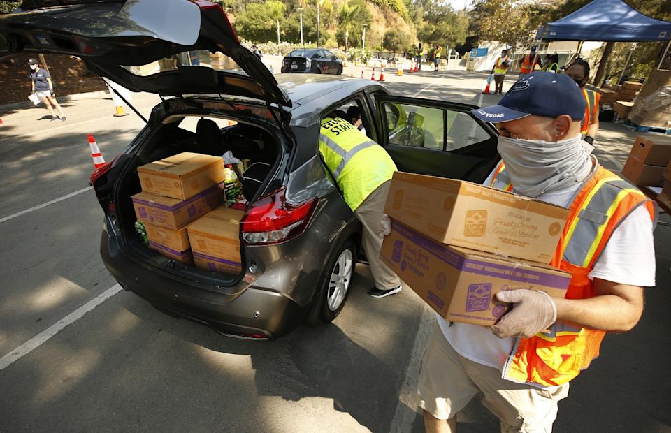 Volunteer Grady Silberman, right, and Beatrice Quesnot load food into vehicles at the Hollywood Bowl.