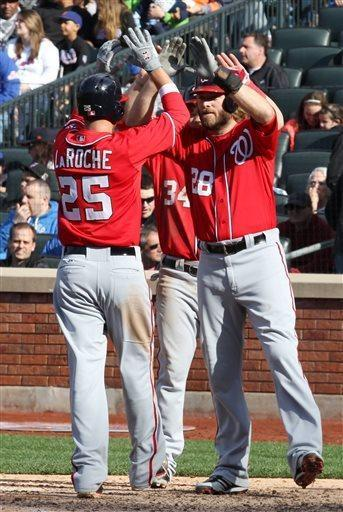 Washington Nationals Jayson Werth, right, and Bryce Harper, center, congratulate teammate Adam LaRoche after he hit a three-run home run in the fifth inning of a baseball game against the New York Mets in New York on Saturday, April 20, 2013. (AP Photo/Peter Morgan)