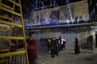 A Palestinian man holds a ladder for another man stringing colored lights on the eve of the Muslim holy month of Ramadan in the Old City of Jerusalem, Monday, April 12, 2021. (AP Photo/Maya Alleruzzo)