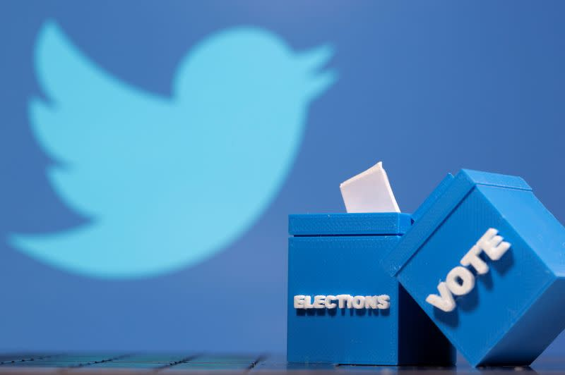3D printed ballot boxes are seen in front of a displayed Twitter logo
