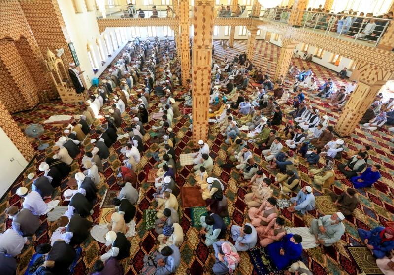 FILE PHOTO: Afghan men take part in prayers during Eid al-Fitr, a Muslim festival marking the end the holy fasting month of Ramadan, at a mosque, amid the spread of the coronavirus disease (COVID-19), in Laghman province
